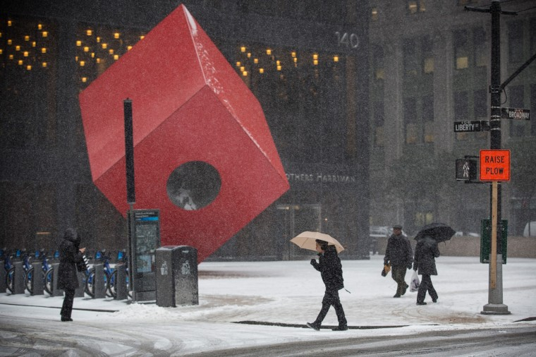 """People walk past the art instalation """"Red Cube"""" by Isamu Noguchi during a snow storm that is moving through the Northeast on January 21, 2014 in New York City. Along with dropping arctic tempertures the storm is expected to bring three to five inches by nightfall, with another four to six inches falling overnight. (Photo by Andrew Burton/Getty Images)"""