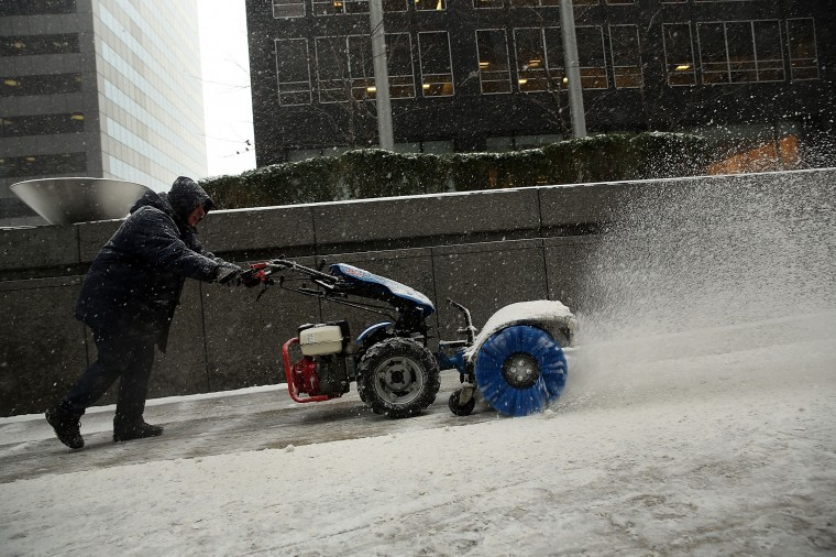Sidewalks are cleared of snow and ice during a snowstorm that is moving through the Northeast on January 21, 2014 in New York City. Along with dropping arctic tempertures the storm is expected to bring three to five inches by nightfall, with another four to six inches falling overnight. (Photo by Spencer Platt/Getty Images)