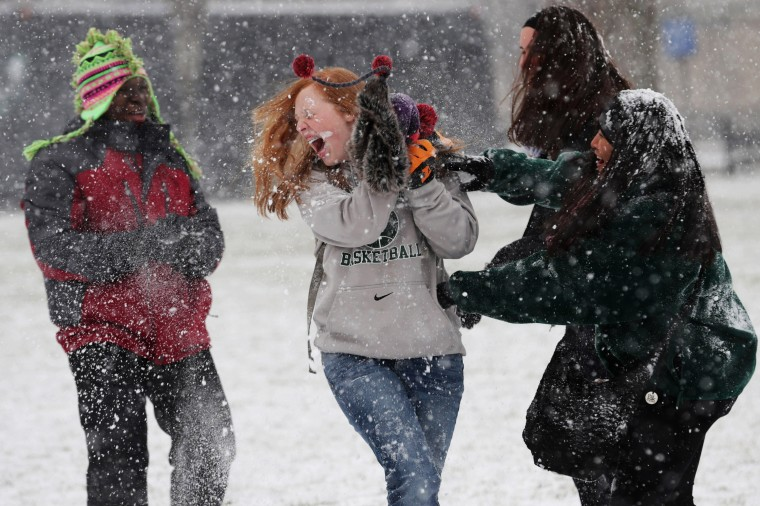Student tourists from Chattanooga, Tennessee, have a snowball fight on National Mall January 21, 2014 in Washington, DC. A strong winter storm is bearing down on the East Coast between Virginia and Massachusetts and could dump four to eight inches of snow on the Washington area. (Photo by Chip Somodevilla/Getty Images)