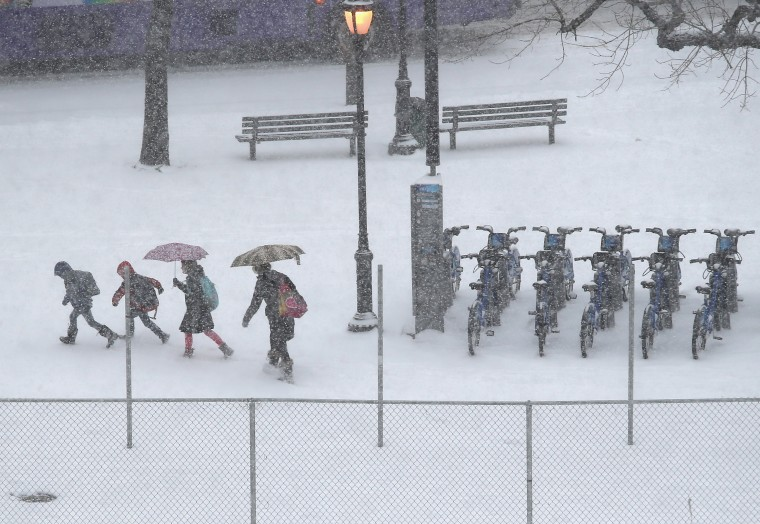 People walk past a CitiBike stand during a snowstorm on January 21, 2014 in New York City. Areas of the Northeast are predicted to receive up to a foot of snow in what may be the biggest snowfall of the season so far. (Photo by John Moore/Getty Images)