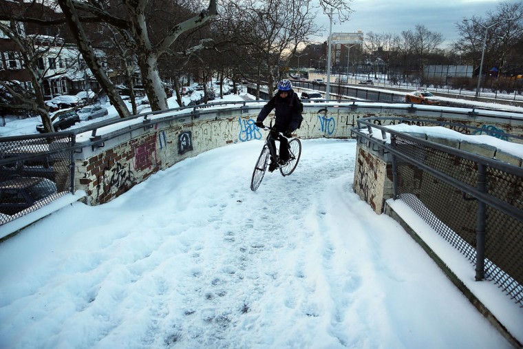 A woman walks over a snow covered foot bridge with her bike in Brooklyn on the morning after a major winter storm blanketed much of New York City in 10 to 12 inches of snow on January 22, 2014 in New York City. While the storm caused major traffic and subway delays, New York City area schools were open on Wednesday morning. (Photo by Spencer Platt/Getty Images)