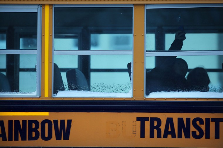 A school bus heads down a snowy road in Brooklyn on the morning after a major winter storm blanketed much of New York City in 10 to 12 inches of snow on January 22, 2014 in New York City. While the storm caused major traffic and subway delays, New York City area schools were open on Wednesday morning. (Photo by Spencer Platt/Getty Images)