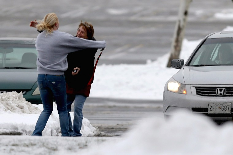 Two women run to embrace each other outside the Columbia Town Center Mall after three people were killed in a shooting there January 25, 2014 in Columbia, Maryland. Police still do not have a motive for the shooting but believe the shooter has been killed. (Photo by Chip Somodevilla/Getty Images)
