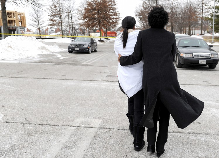 Two women console one another other outside the Columbia Town Center Mall after three people were killed in a shooting there January 25, 2014 in Columbia, Maryland. Police still do not have a motive for the shooting but believe the shooter has been killed. (Photo by Patrick Smith/Getty Images)