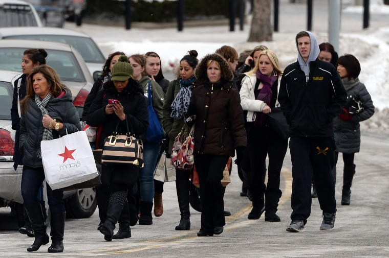 People walk outside of Columbia Town Center Mall after three people were killed in a shooting there January 25, 2014 in Columbia, Maryland. Police still do not have a motive for the shooting but believe the shooter has been killed. (Photo by Patrick Smith/Getty Images)