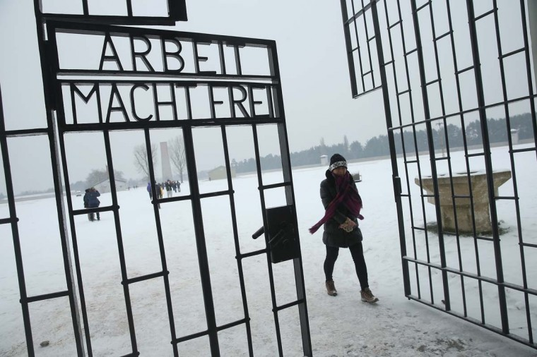 "A visitor walks past an inscription that reads: ""Arbeit Macht Frei,"" which means ""Work Leads To Freedom,"" at a gate at the Sachsenhausen concentration camp memorial on Holocaust Memorial Day on January 27, 2014 in Oranienburg, Germany. Sachsenhausen operated from 1933 until 1945 as a concentration camp run by the Nazis where political opponents, Jews and Soviet prisoners of war were imprisoned and many of them murdered. Germany is commemorating the Holocaust today with a variety of events across the country. (Sean Gallup/Getty Images)"