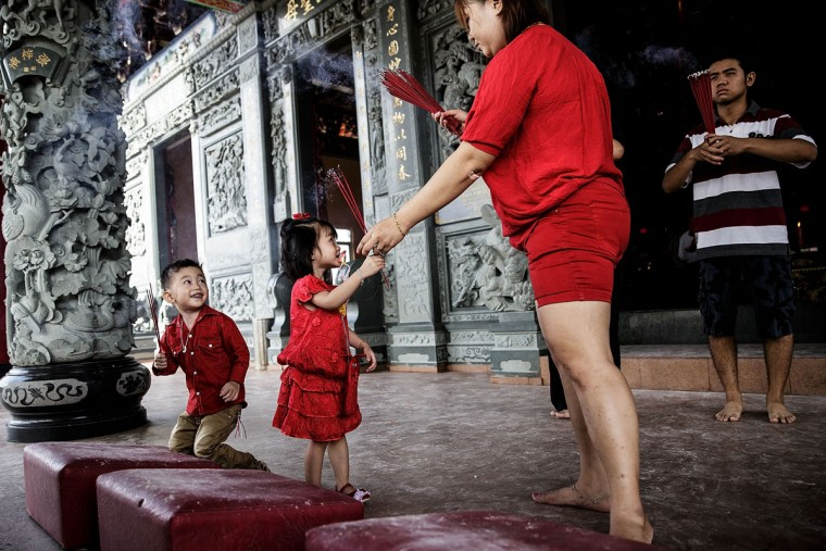 Two kids hold incense sticks as they attend prayers during Chinese New Year celebrations for the Year of The horse at Satya Dharma Temple on January 31, 2014 in Denpasar, Bali, Indonesia. Thousands gathered today to celebrate the Chinese New Year and welcome the Year of the Horse, with new year's day falling on January 31st. Chinese new Year is the most important festival in the Chinese calendar and is widely celebrated across Asia. (Photo by Agung Parameswara/Getty Images)