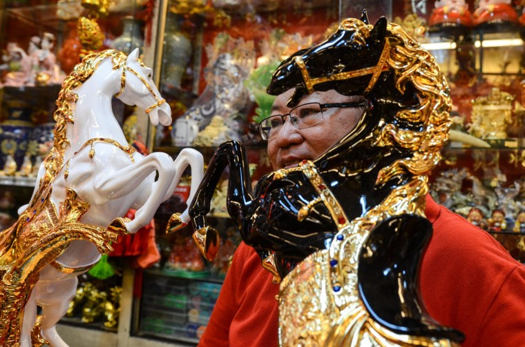 A merchant displays a figurine of a horse in the Chinese district of Binondo on January 31, 2014 in Manila, Philippines. Thousands gathered today to celebrate the Chinese New Year and welcome the Year of the Wooden Horse, with New Year's Day which falls on January 31, 2014. Chinese new Year is the most important festival in the Chinese calendar and is widely celebrated across Asia. (Photo by Dondi Tawatao/Getty Images)