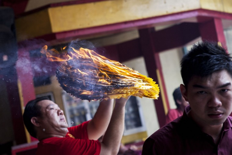 A man holds votive paper and burns it as they attend prayers during Chinese New Year celebrations for the Year of The Horse at Bun San Bio Temple on January 31, 2014 in Tangerang, Indonesia. Indonesian Chinese today are celebrating the Chinese New Year and welcoming the Year of the Horse, with new year's day falling on January 31st. Chinese new Year is the most important festival in the Chinese calendar and is widely celebrated across Asia. (Photo by Oscar Siagian/Getty Images)