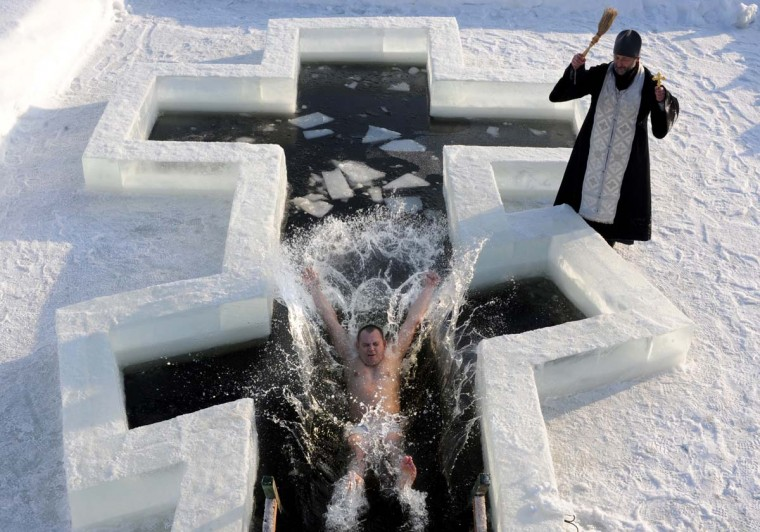 A Belarus Orthodox believer plunges into icy waters as a priest blesses him on the eve of the Epiphany holiday in Pilnitsa some 30 km outside Minsk, on January 18, 2013. Thousands of believers jumpe into holes cut in ice, braving freezing temperatures, on January 18 and early on January 19 to mark Epiphany, when they take part in a baptism ceremony. (Viktor Drachev/AFP/Getty Images)