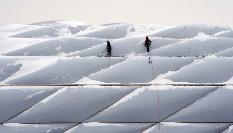 Two men with climbing gear and equipment remove snow from the bright plastic shell of the Allianz Arena on January 18, 2013 in Munich, southern Germany. (Peter Kneffel/AFP/Getty Images)