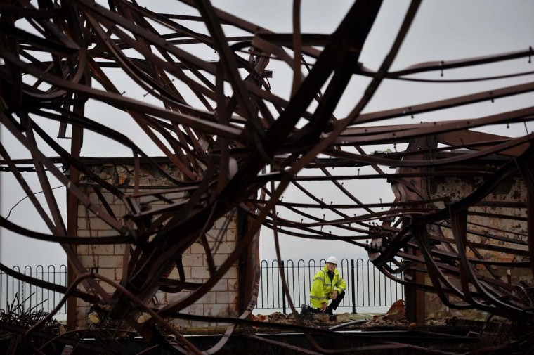 Pier restoration starts: Project manager David Spooner surveys the tangled burnt-out remains of the ballroom on Hastings Pier in Hastings, southern England, on December 13, 2013 ahead of the start of a multi-million pound regeneration project. Hastings Pier was originally constructed in opulent style in the late 19th century, seeing its heyday in the 1930s and hosting music concerts by major artists including The Rolling Stones in the 1960s and 70s. After undergoing various additions and re-construction to repair storm and fire damage throughout the 20th century, the Victorian pier finally suffered a devastating fire in 2010 that destroyed much of the superstructure and leaving just a burnt out shell. Following a Heritage Lottery Fund (HLF) grant and money from other funds, a 14 million GBP regeneration project is set to begin work on January 6. (BEN STANSALL/AFP/Getty Images)