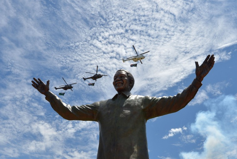 Helicopters carrying the South African flag fly over a 9-meter bronze statue of South African former president Nelson Mandela which was unveiled on December 16, 2013 on the lawns of the Union Buildings, the seat of government in Pretoria where Mandela was inaugurated as South Africa's first black president in 1994. On a public holiday dedicated to reconciliation, South Africans on Monday started coming to terms with the loss of Nelson Mandela, a day after he was buried at the end of a life struggle for freedom and equality. (Alexander Joe/AFP/Getty Images)