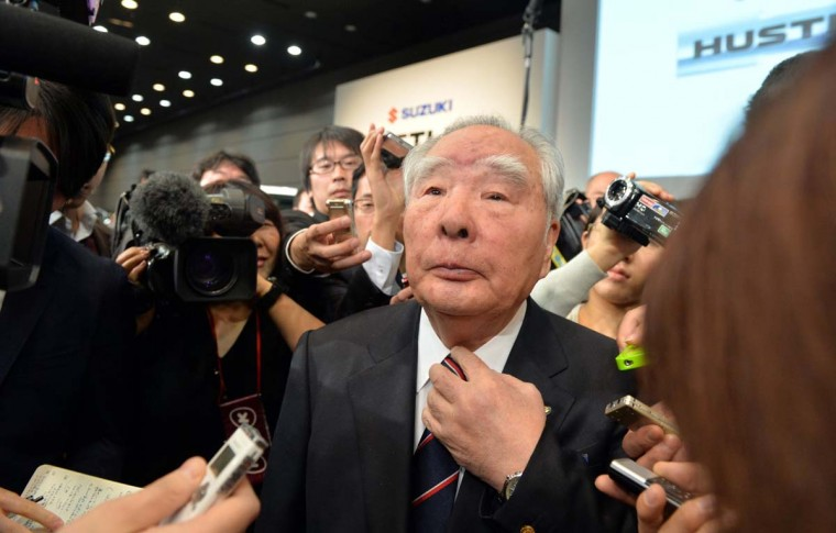 "Auto debut: The president of Japanese auto maker Suzuki Motor, Osamu Suzuki, is surrounded by the media after introducing the company's new mini sports utility vehicle, called ""Hustler,"" at a news conference in Tokyo on December 24, 2013. The Hustler, equipped with a 660cc engine, will go on sale from January 8. (SHIKAZU TSUNO/AFP/Getty Images)"