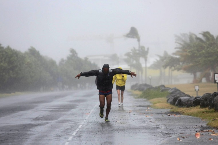 A man faces fierce winds on January 2, 2014 in Le Port, in the French La Reunion overseas island. The Indian Ocean island is placed on red-alert today, due to the Bejisa hurricane with gusts between 120 and 150 km per hour and may even exceed 200 km per our on the reliefs exposed. In early afternoon (13h19GMT), the storm made its first casualties - one serious and seven light - and its first damages, including more than 80,000 homes without electricity. (Richard Bouhet/AFP/Getty Images)