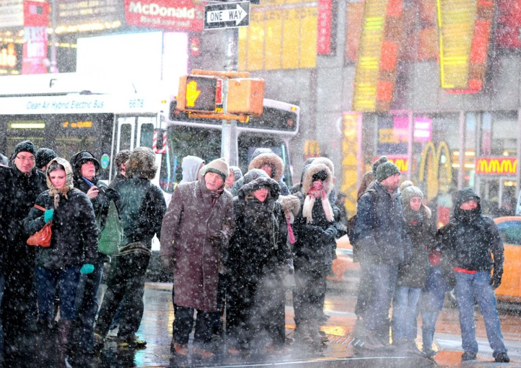 Pedestrians stand in the snow at 7th Avenue on Times Square January 2, 2014 in New York. (DON EMMERT/AFP/Getty Images)