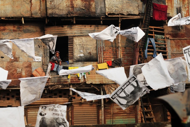 A Bangladesh resident of a shanty town looks out of a window of her home at a street filled with political posters in Dhaka on January 3, 2014. Bangladesh's main opposition party has called for a non-stop blockade, rejecting plans for a January 5, election and plunging the nation into fresh political turmoil. (Munir Uz Zaman/AFP/Getty Images)