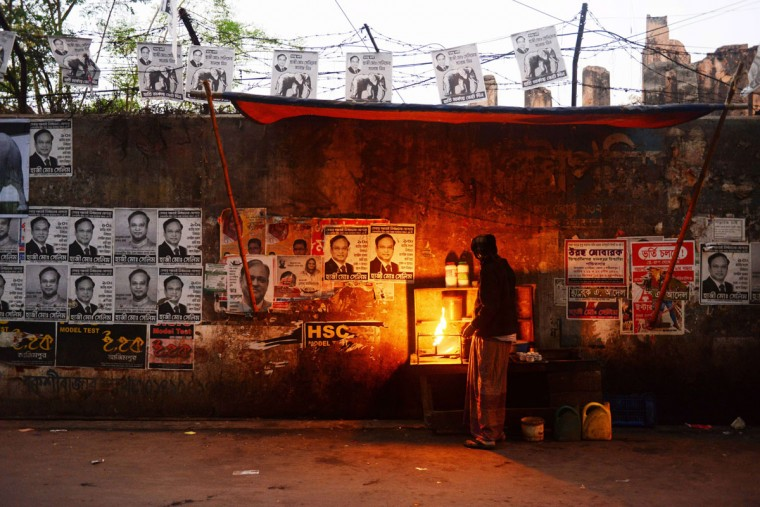 A Bangladeshi vendor tends to his road side stall next to political posters afixed on a wall in the old city of Dhaka on January 3, 2014. Sheikh Hasina, the 66-year-old prime minister of Bangladesh, the daughter of the nation's founder, is certain to win a new five-year term when Bangladesh holds its 10th parliamentary elections without any of her opponents standing. Bangladesh's main opposition party has called for a non-stop blockade, rejecting plans for a January 5 election and plunging the nation into fresh political turmoil. (Roberto Schmidt/AFP/Getty Images)
