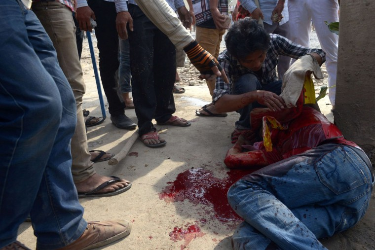 A Cambodian worker (R) lies wounded during clash with military police during a garment workers' protest to demand higher wages in front of a factory in Phnom Penh on January 3, 2014. Cambodian police opened fire on protesting garment workers on the outskirts of the capital Phnom Penh on January 3, leaving several people wounded, according to an AFP photographer. (Tang Chhin Soth/AFP/Getty Images)