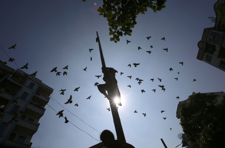 Birds fly over as a man climbs a pole to reach a flag in a popular game to mark Myanmar's 66th Independence Day in Yangon on January 4, 2014. Myanmar gained independence from Britain on January 4, 1948. (Ye Aung Thu/AFP/Getty Images)