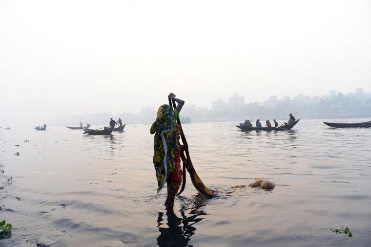 A Bangladeshi resident of a depressed neighbourhood washes clothing in the waters of the Buriganga river in Dhaka on January 4, 2014. About a third of Dhaka's 15 million residents live in poverty. (Roberto Schmidy//AFP/Getty Images)