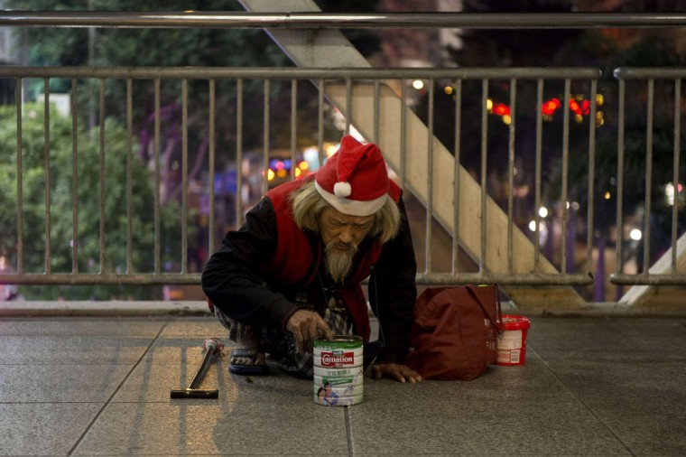 A man wearing a Santa Claus hat checks his collection tin as he begs for money in Hong Kong on January 4, 2014. There are 1.31 million people in the southern Chinese city living below the poverty line, a rate of 19.6 percent, according to the most recent government data available from 2012. The introduction of a benchmark to measure poverty, in September 2013, was hailed as a significant move to tackle the issue for a densely populated metropolis known for its sky-high rents and home to one of largest wealth gaps in the world. (Alex Ogle/AFP/Getty Images)