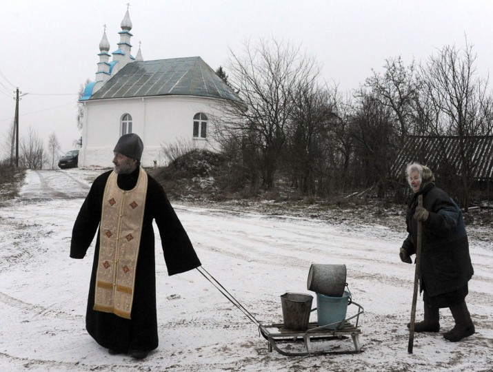 A Belarussian Orthodox priest helps an eldery woman carry water buckets in the village of Kasun, some 30 kilometres west of Minsk, on January 3, 2014. (Viktor Drachev/AFP/Getty Images)