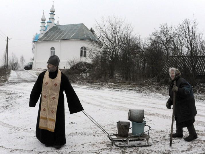 A Belarussian Orthodox priest helps an eldery woman carry water buckets in the village of Kasun, some 30 kilometres west of Minsk, on January 3, 2014. (Viktor Drachev/AFP/Getty Images)
