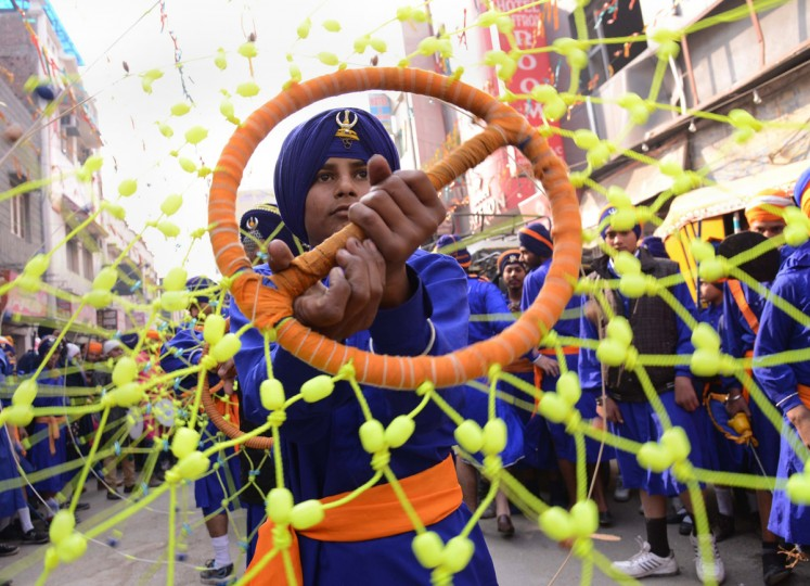An Indian Sikh Nihang, or warrior, performs Gatka martial arts skills during a procession at the Golden Temple in Amritsar on January 6, 2014, as part of birth anniversary celebrations of Guru Gobind Singh. The birth anniversary of Guru Gobind Singh, the tenth Sikh guru, is marked on January 6. (Narinder Nanu/AFP/Getty Images)