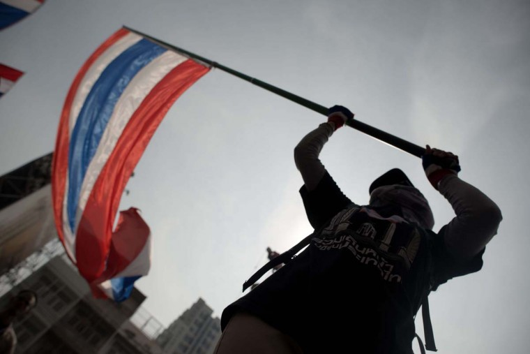"Thais voice dissent: A Thai anti-government protester waves the national flag during a rally in Bangkok on January 7, 2014. Demonstrators, who are seeking to curb the political dominance of Prime Minister Yingluck Shinawatra's billionaire family, say they will ""shut down"" Bangkok from January 13. (NICOLAS ASFOURI/AFP/Getty Images)"