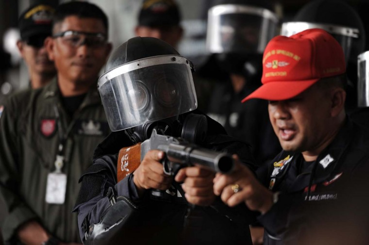 ... and police bluster: A Thai policeman (center) holds a rifle used to fire tear gas canisters as police demonstrate crowd-control techniques in anticipation of a planned anti-government rally at the Police Club in Bangkok on January 7, 2014. (CHRISTOPHE ARCHAMBAULT / AFP/Getty Images)