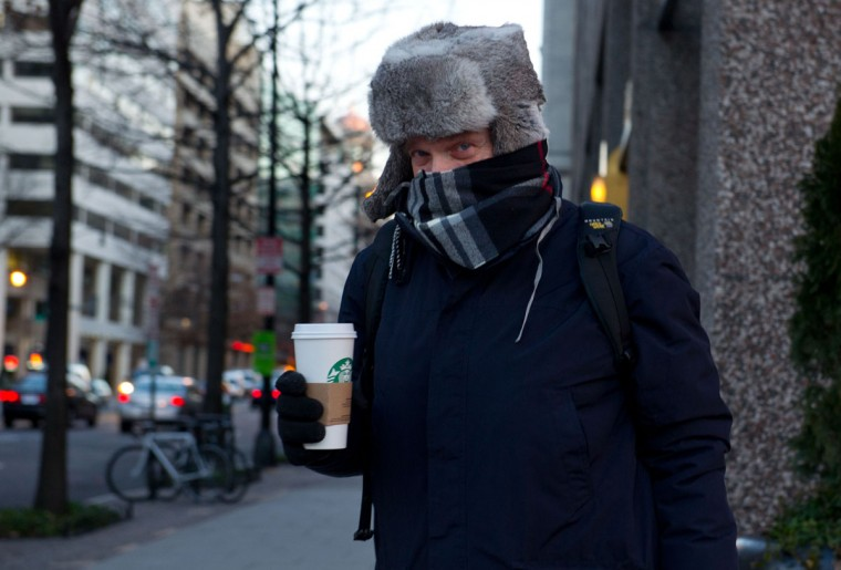 A man bundled against the cold leaves a Starbucks with a hot coffee as temperatures dipped into the single digits Fahrenheit and minus degrees with the wind chill on January 7, 2014 in Washington, DC. (KAREN BLEIER/AFP/Getty Images)