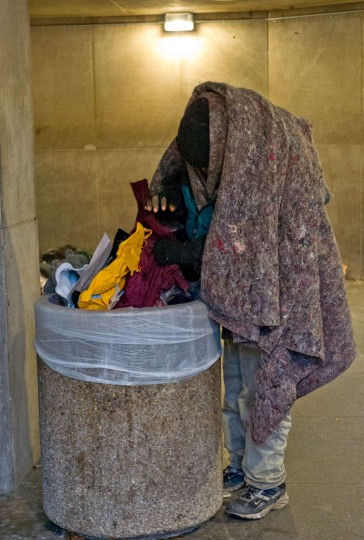 A homeless man bundled against the cold goes through the trash as temperatures dipped into the single digits Fahrenheit and minus degrees with the wind chill on January 7, 2014 in Washington, DC. (KAREN BLEIER/AFP/Getty Images)
