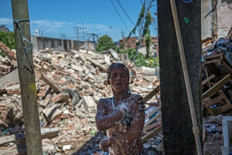 Valeria da Silva, 38-year-old and mother of 8 children, takes a shower in front of demolished area, including her house, at Metro favela (shantytown) near Maracana Stadium in Rio de Janeiro, Brazil, on January 8, 2014. The favela's families were expropriated under city's improved plan before the World Cup and the Olympics in 2010. (Yasuyoshi Chiba/AFP/Getty Images)