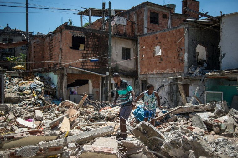 Nilvaldo Franca (L) looks for materials to sell with his nephew, at a demolished area including his home, at Metro favela (shantytown) near Maracana Stadium in Rio de Janeiro, Brazil, on January 8, 2014. The favela's families were expropriated under city's improved plan before the World Cup and the Olympics in 2010. (Yasuyoshi Chiba/AFP/Getty Images)