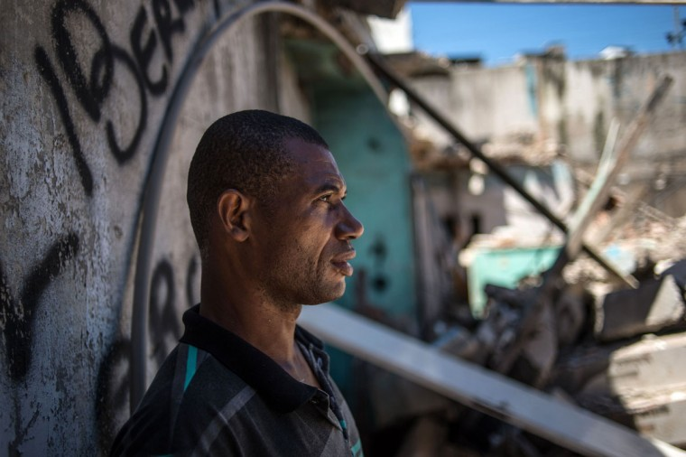 Nilvaldo Franca (L) looks at a demolished area including his home at Metro favela (shantytown) near Maracana Stadium in Rio de Janeiro, Brazil, on January 8, 2014. The favela's families were expropriated under city's improved plan before the World Cup and the Olympics in 2010. (Yasuyoshi Chiba/AFP/Getty Images)