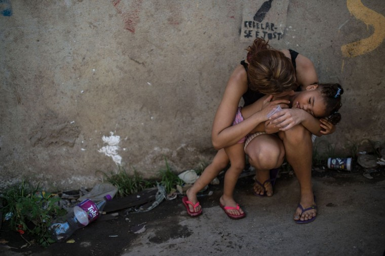 A girl is hugged by her mother at Metro favela (shantytown) near Maracana Stadium in Rio de Janeiro, Brazil, on January 8, 2014. The favela's families were expropriated under city's improved plan before the World Cup and the Olympics in 2010. (Yasuyoshi Chiba/AFP/Getty Images)