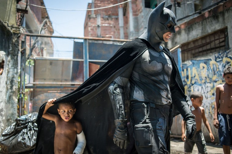 Children play around a man disguised as Batman at the Favela do Metro slum, area just near the Maracana stadium, in Rio de Janeiro, Brazil, on January 9, 2014. Families living in this shantytown within a stone's throw of Rio 's mythical Maracana stadium refuse to have their homes demolished as part of a project to renovate the district before the FIFA World Cup circus pitches camp in June. (Yasuyoshi Chiba/AFP/Getty Images)