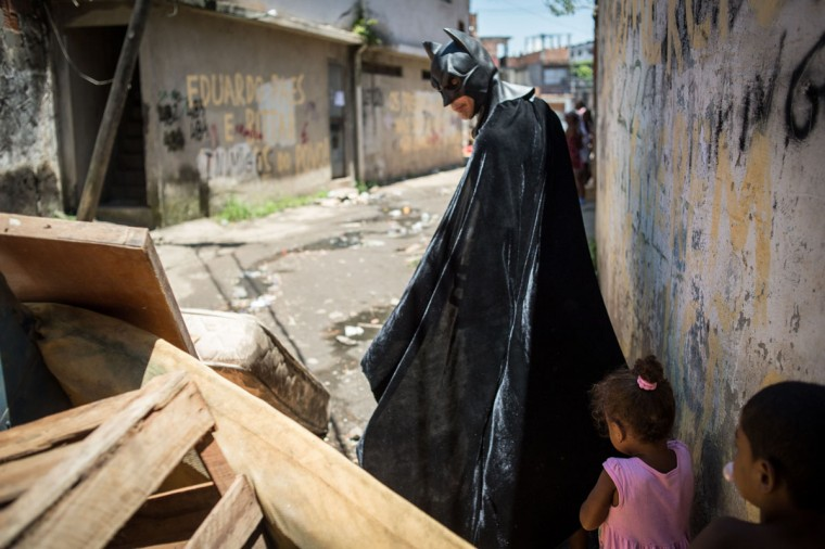 A man disguised as Batman looks at a barricade set up by residents of the Favela do Metro slum, area just near the Maracana stadium, in Rio de Janeiro, Brazil, on January 9, 2014. Families living in this shantytown within a stone's throw of Rio 's mythical Maracana stadium refuse to have their homes demolished as part of a project to renovate the district before the FIFA World Cup circus pitches camp in June. (Yasuyoshi Chiba/AFP/Getty Images)