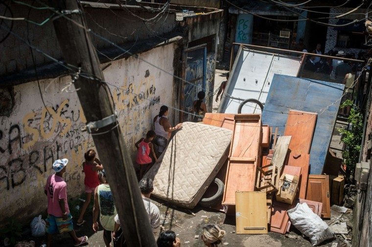 Residents of the Favela do Metro slum, area just near the Maracana stadium, leave through an entrance almost blocked by a barricade they have lifted, in Rio de Janeiro, Brazil, on January 9, 2014. Families living in this shantytown within a stone's throw of Rio 's mythical Maracana stadium refuse to have their homes demolished as part of a project to renovate the district before the FIFA World Cup circus pitches camp in June. (Yasuyoshi Chiba/AFP/Getty Images)