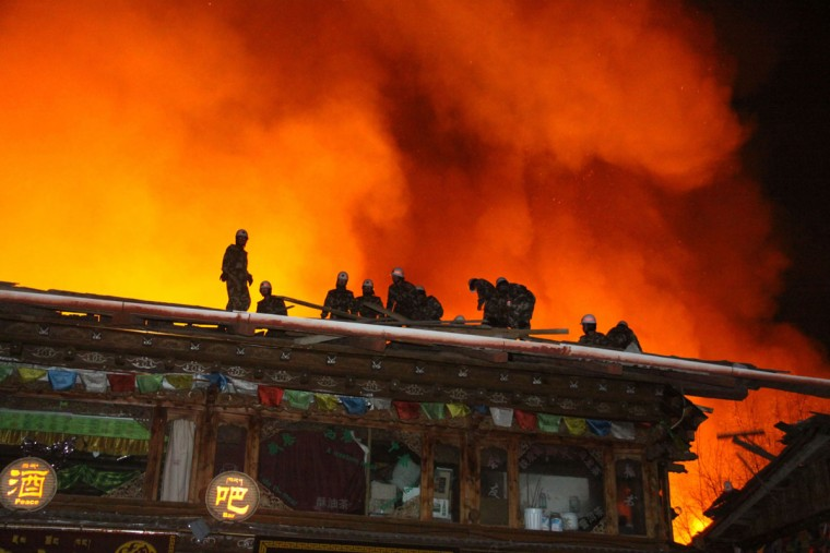 Firefighters work to put out a fire in the ancient Tibetan village of Dukezong in Shangri-La county, southwest China's Yunnan province on November 11, 2014. An ancient Tibetan village in the popular tourist area of Shangri-La in China's southwest Yunnan province has been partially destroyed in a giant inferno, state media reported. (China Out/AFP/Getty Images)