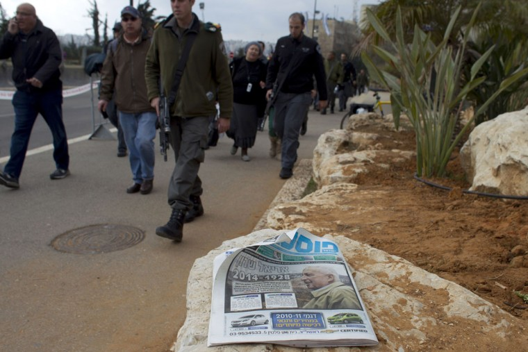 Israeli security forces walk past a newspaper with a picture of late former prime minister Ariel Sharon on the front page, on January 12, 2014, in Jerusalem. Israeli media lavished praise on Sharon, who died the previous day in hospital after eight years in a coma. (Ahmad Gharabli/AFP/Getty Images)
