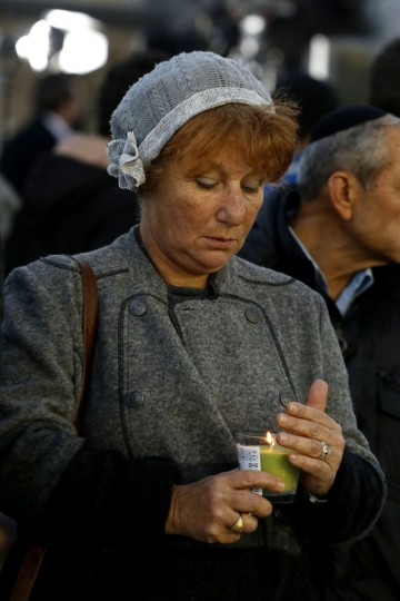 An Israeli woman holds a candle in memory of former prime minister Ariel Sharon as Israelis pay their last respects next to his coffin in Jerusalem on January 12, 2014. (Gali Tibbon/AFP/Getty Images)