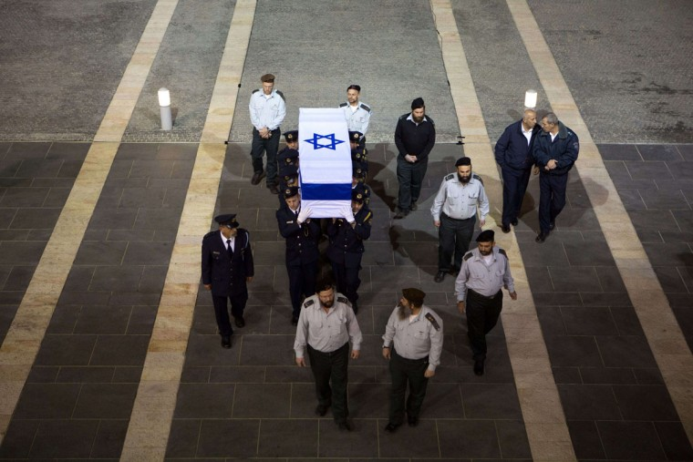 Israeli honor guards carry the coffin of former prime minister Ariel Sharon in to the Knesset (the Israeli Parliament) in Jerusalem at the end of the day on January 12, 2014, as Israelis came to pay their respects. Celebrated as a military hero by some, recognized as a pragmatic politician by others and despised as a bloodthirsty criminal by his foes, Sharon was a polarizing figure at home and abroad. (Menahem Kahana/AFP/Getty Images)