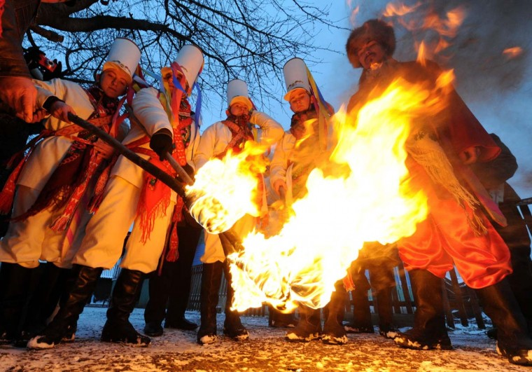 "Local residents dressed in Belarussian traditional costumes hold torches as they perform traditional ""Koliady"" rituals on January 13, 2014 in the village of Semezhevo, some 160 km south of Minsk. Koliady is an ancient pagan holiday initially celebrated on winter solstice but since appropriated to celebrate Christmas, Julian calendar's New Year, and other winter holidays. (Viktor Drachev/AFP/Getty Images)"