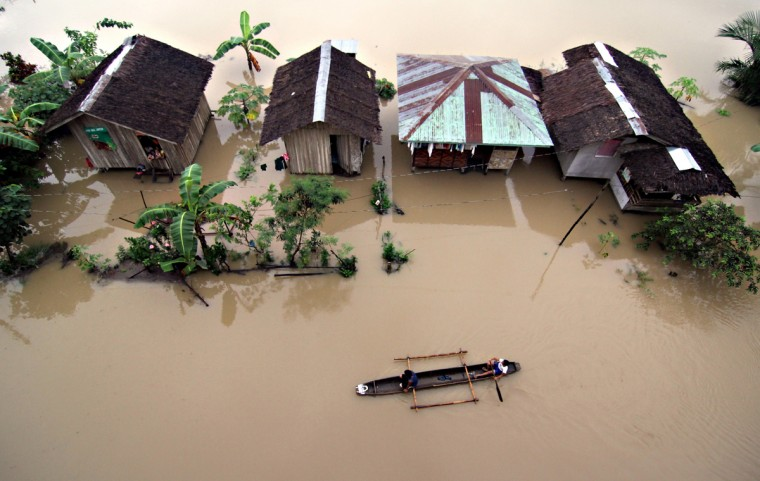 Residents ride a wooden boat as they paddle past submerged houses due to flooding brought about by heavy rains in the outskirts of Butuan City, Agusan del sur province, in southern island of Mindanao on January 13, 2014. Twenty-two people have been killed and nearly 200,000 others evacuated from floods and landslides that hit a southern Philippine region still recovering from a deadly 2012 typhoon, the government said January 14. (Erwin Mascarinas/AFP/Getty Images)