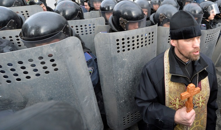 An Orthodox priest holds a cross in front of riot policemen standing guard in front of the parliament's building in Kiev on January 14, 2014, as Ukrainian veterans and invalids of Chernobyl's nuclear disaster try to give their demandings to the parliamentary leadership. They protest against the adoption by parliament of the state budget for 2014, which does not provide financing of social programs for the Chernobyl's veterans and the invalids. (Sergei Supinsky/AFP/Getty Images)