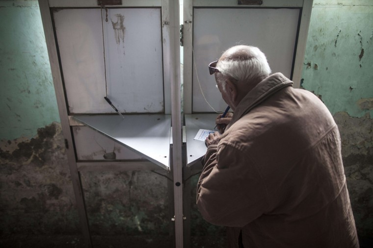 An Egyptian man casts his vote on a new constitution in the Al-Haram neighbourhood in the southern Cairo Giza district on January 14, 2014. The military-installed government implored voters to turn out en masse to ratify the constitution, with the country's lingering polarisation underscored by the explosion of a small bomb in Cairo that caused no injuries. (Mahmoud Khaled/AFP/Getty Images)