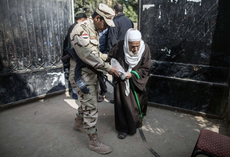 An Egyptian man is assisted to walk as he arrives at a polling center to vote on a new constitution in Al-Haram in the southern Cairo Giza district on January 14, 2014. The military-installed government implored voters to turn out en masse to ratify the constitution, with the country's lingering polarisation underscored by the explosion of a small bomb in Cairo that caused no injuries. (Mahmoud Khaled/AFP/Getty Images)