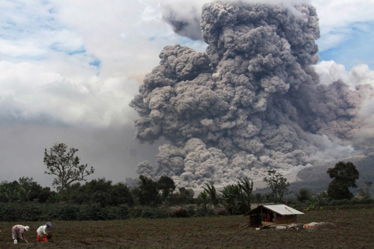 Villagers tend to crops as the Sinabung volcano behind them spews hot ash in Karo, Indonesia on January 14, 2014. More than 25,000 people have fled their homes following a series of eruptions and lava flows from Sinabung volcano in North Sumatra, an official said on January 12. (Kharisma Tarigan/AFP/Getty Images)